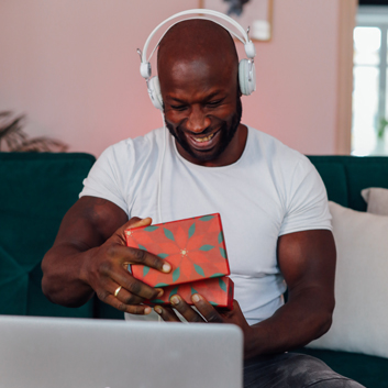 A man smiles while taking the lid off of a gift box during a video chat