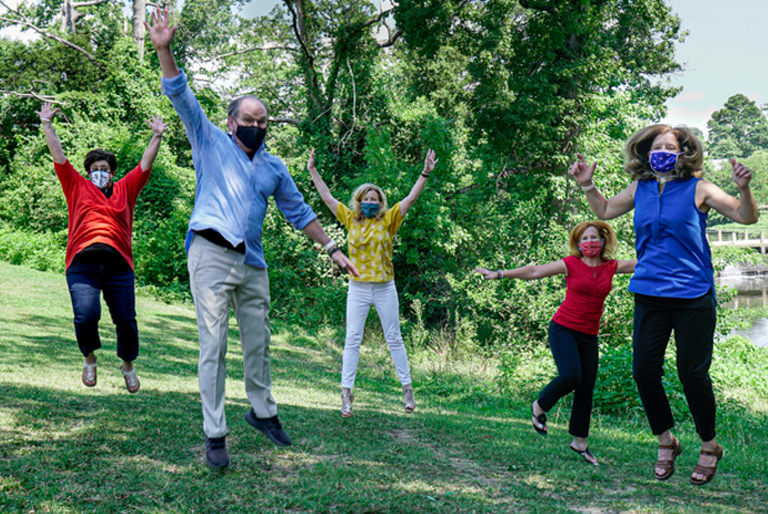 enCircle leadership team jumping in the air in an outdoor setting